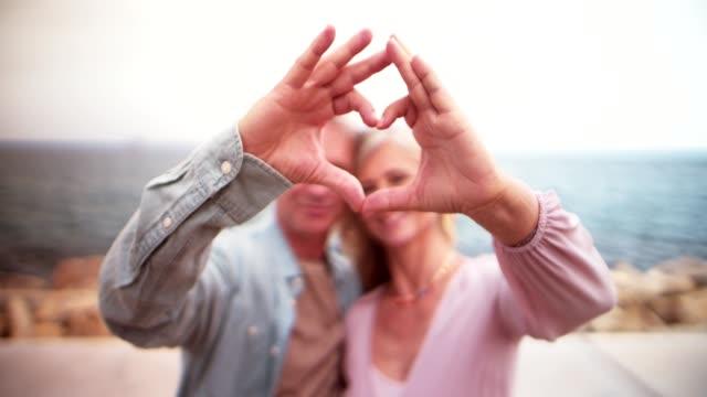 romantiska senior par att göra ett hjärta form med sina händer - hjärtform bildbanksvideor och videomaterial från bakom kulisserna