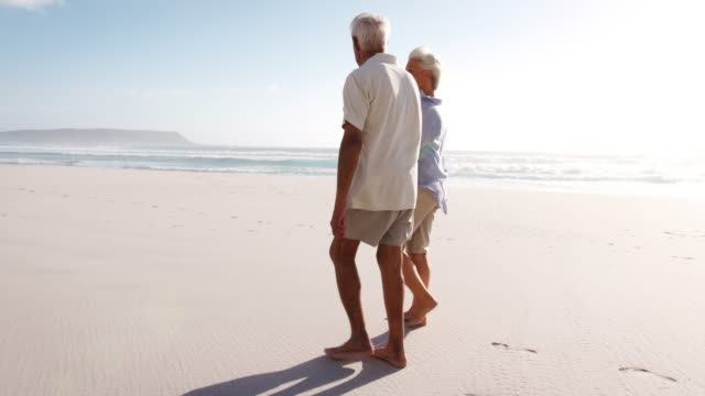 romantic senior couple on summer vacation walking along beach - coppia anziana video stock e b–roll