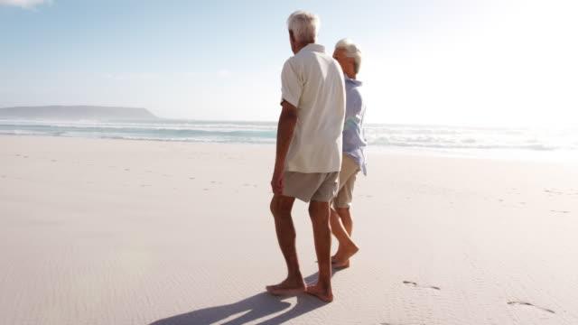 romantiska senior par på sommaren semester promenader längs stranden - senior walking bildbanksvideor och videomaterial från bakom kulisserna