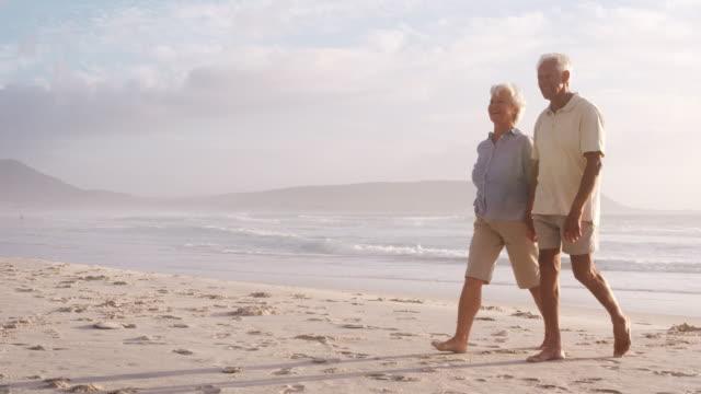 夏休みビーチに沿って歩くにロマンチックなシニア カップル - 老夫婦点の映像素材/bロール
