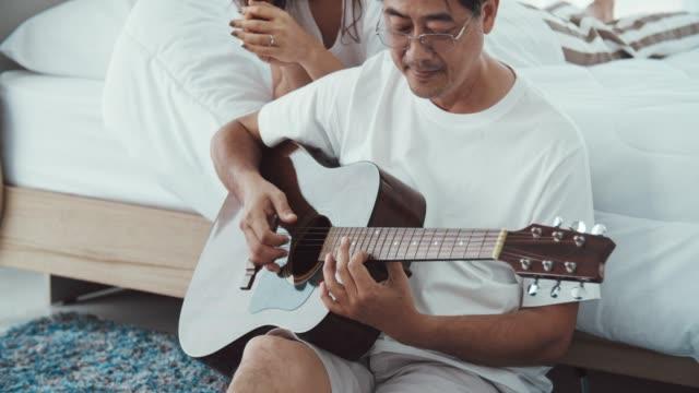 Homme aîné romantique jouant la guitare pour la belle femme aînée - Vidéo