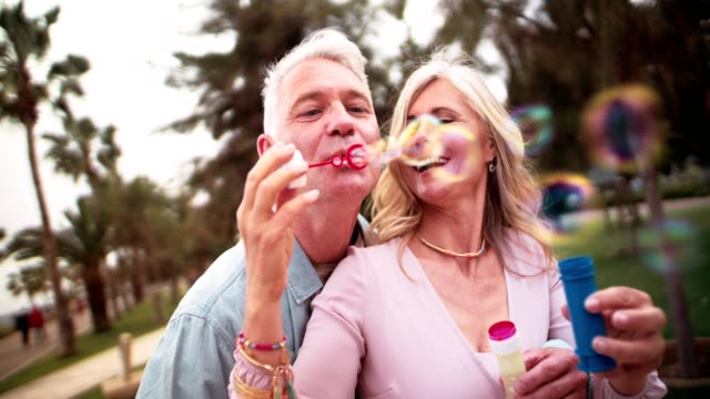 Romantic seniors in a relationship blowing bubbles in the park video