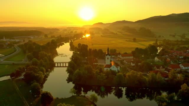 vídeos y material grabado en eventos de stock de aerial romántico pequeño pueblo en el río al atardecer - drone footage