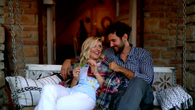 Romantic sunset at the porch. Closeup front of a happy couple on a rustic porch swing at a vacation house. They are spending romantic sunset together, talking and enjoying their getaway weekend. porch stock videos & royalty-free footage