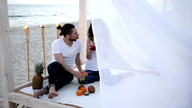 romantic trip, happy friends with cocktails, an exotic vacation in bungalow, on background tropical fruits, burning torches and beautiful beach video