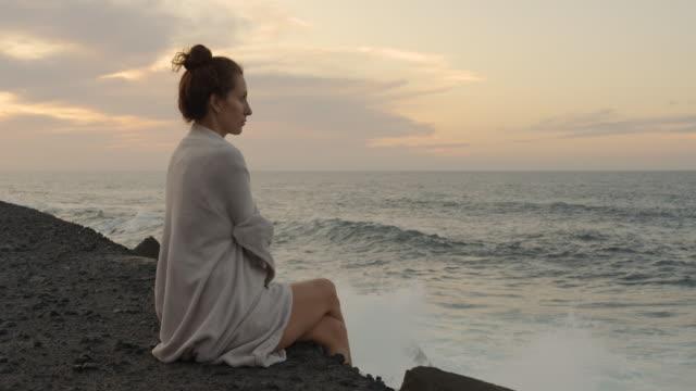 Romantisch wit Europees meisje dat op de grote reusachtige rots zit. Het getijde van de oceaan bij zonsondergang op het strand video