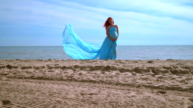 Romantic woman in blue dress on beach. Pregnant woman holding belly