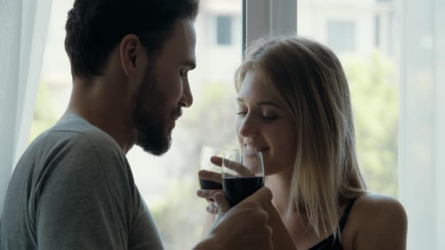 Romantic young couple drinking wine Handheld shot of romantic young couple standing near the window kissing to each other while drinking wine, 4K Resolution falling in love stock videos & royalty-free footage