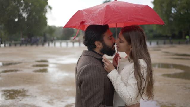 a romantic young couple together under an umbrella in the rain kissing - true love angielski zwrot filmów i materiałów b-roll