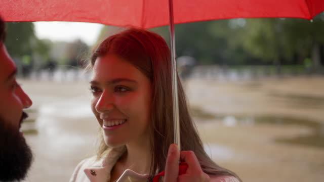 romantyczna młoda para razem pod parasolem w deszczu patrząc i smilling na siebie - true love angielski zwrot filmów i materiałów b-roll