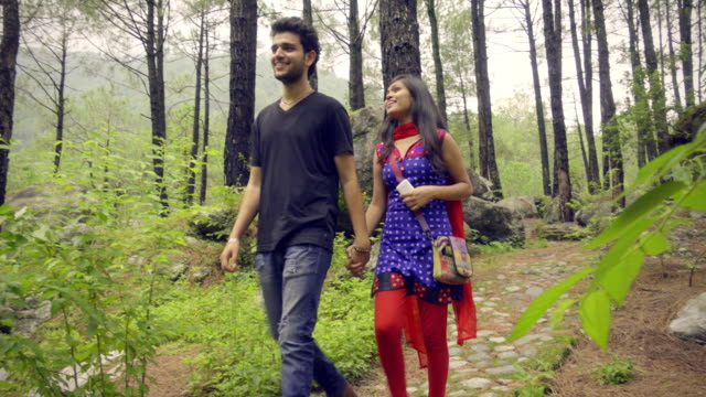 Romantic young couple walking in nature parkland. video