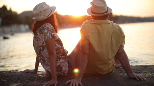 Romantic young couple watching sunset by the sea Two young people enjoying sunset and each other on the pier in the sea face to face stock videos & royalty-free footage