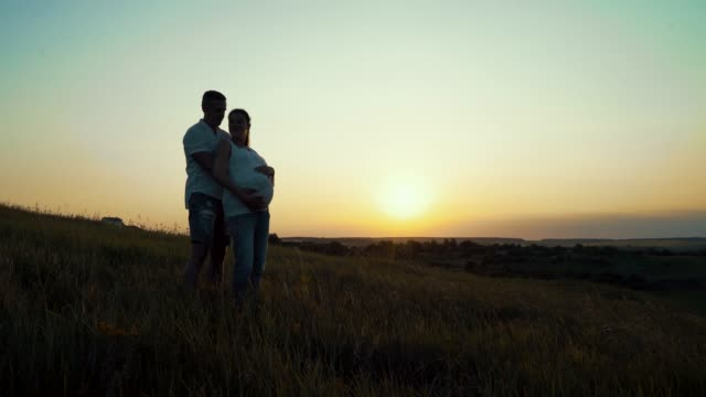Romantic young happy pregnant couple hugging in nature at sunset