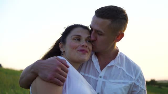 romantiska unga glada gravida par kramar i naturen vid solnedgången - make bildbanksvideor och videomaterial från bakom kulisserna