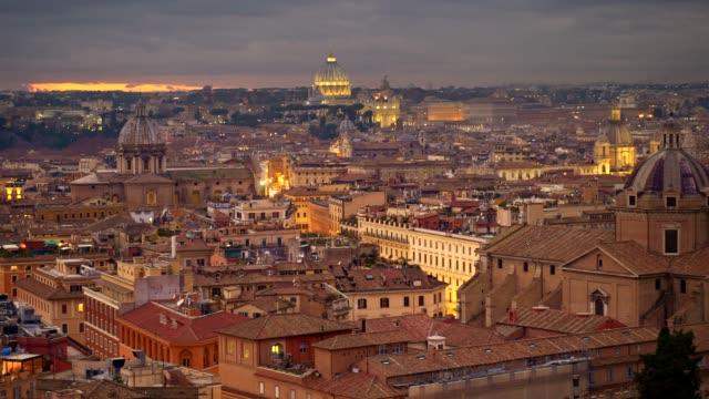 vidéos et rushes de rome, italie.  panoramique tourné du centre de la vieille ville de rome après le coucher du soleil. maisons lumineuses et cathédrale saint-pierre au vatican, rome. 4k, uhd - rome