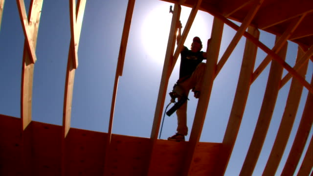 Roof Building Framing Carpenter The halo glow of the sun silhouettes a framing carpenter as he works at building a house roof carpenter stock videos & royalty-free footage