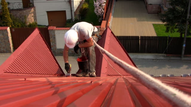 Roof painting Painting roof of a private house with safety rope  house painter stock videos & royalty-free footage