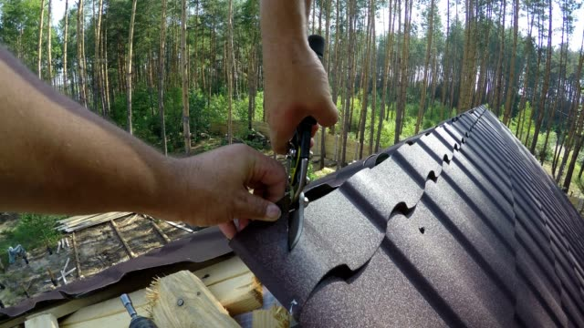 Roofer cuts roofing metal material. video