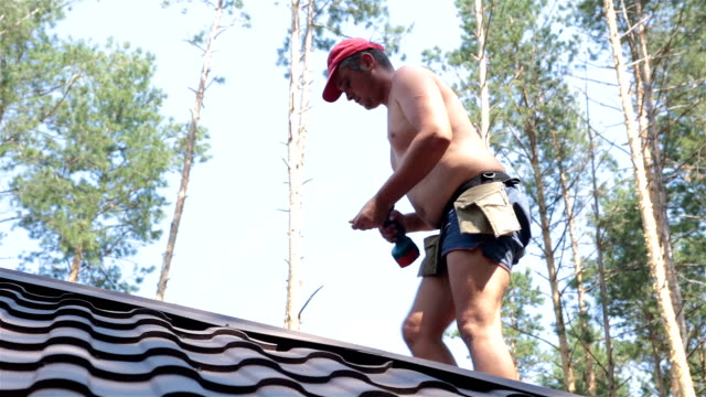 roofer fastens metal roofing material. - imprenditore edile video stock e b–roll