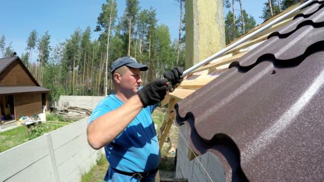 roofer gör mätningar av taket. - yttertak bildbanksvideor och videomaterial från bakom kulisserna