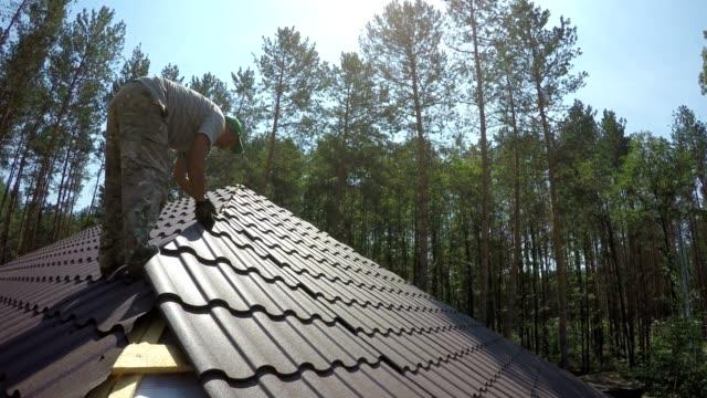 vídeos de stock e filmes b-roll de roofer puts the metal roofing material on the roof. - telhado