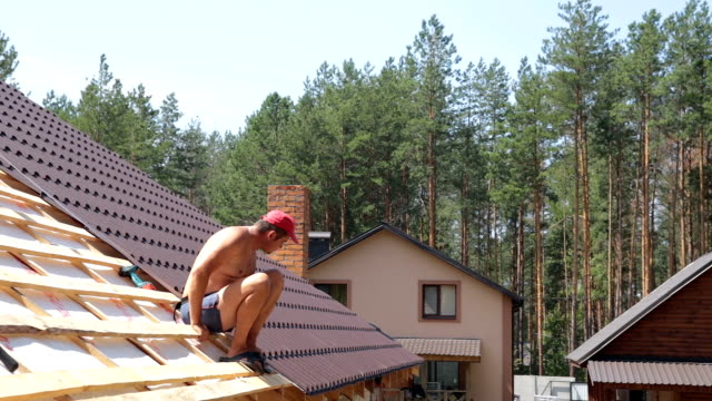 Roofer sits on the roof and performs a control measurement. video