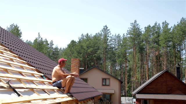 Roofer sits on the roof. video