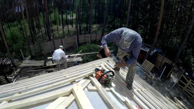 Roofer with a chainsaw on the roof. video