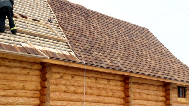 Roofer working on unfinished pine tared video