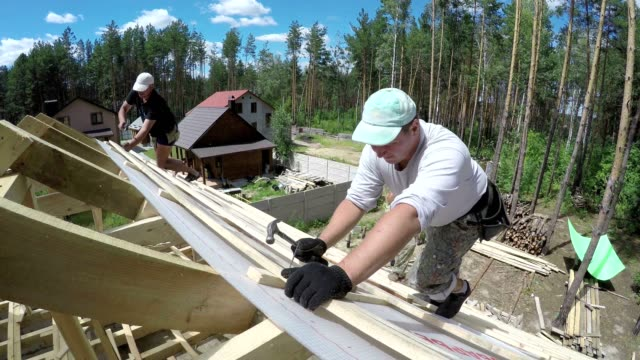 Roofers are hammering nails into a plank on the roof.