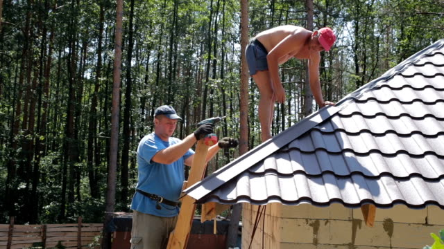 Roofers fasten metal roofing material to the corners of the roof. video