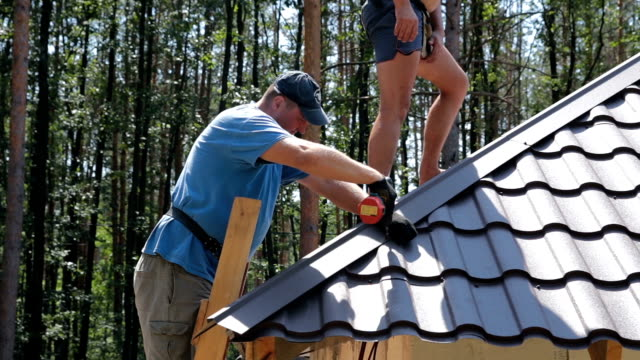 Roofers fasten metal roofing material. video