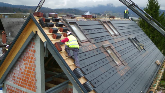 AERIAL Roofers laying tiles on a new house