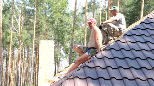 Roofers rest on the roof. video