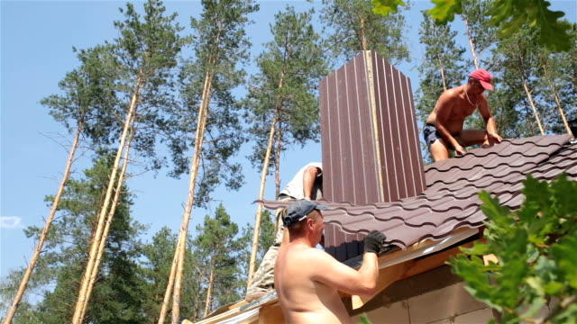 Roofers work on the roof near the chimney. video