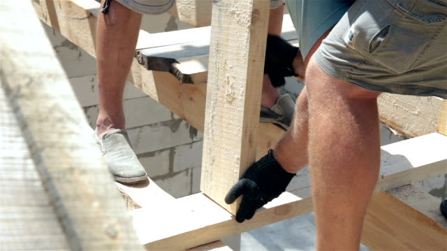 Roofers work on the roof. The builder hammers the nails with a hammer. video
