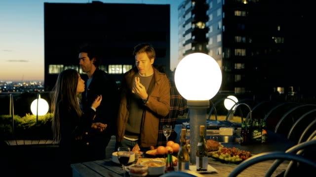 auf dem dach party nach einbruch der dunkelheit - dachgarten videos stock-videos und b-roll-filmmaterial