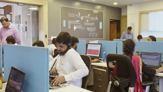 Room Full of Indian Office Workers Sitting at Computers