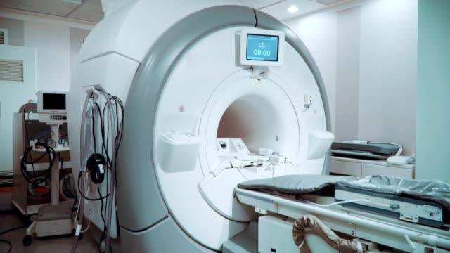 vídeos de stock e filmes b-roll de room with white magnetic resonance tomograph for examination - instrumento para diagnóstico