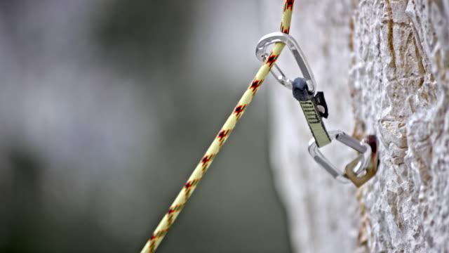 stockvideo's en b-roll-footage met slo mo touw glijden door middel van een quickdraw in de rotswand - touw