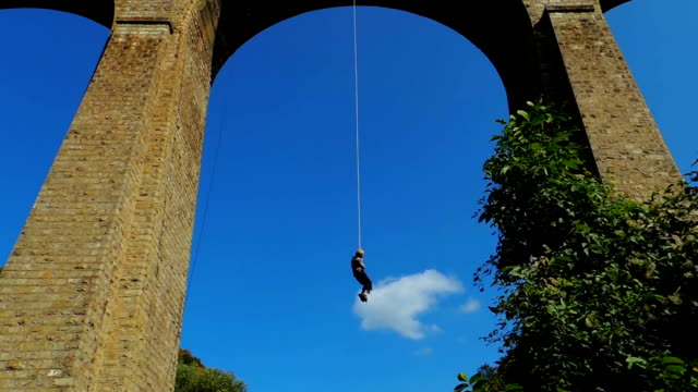 rope jumping from high altitude of bunovo bridge. brave mature woman flying in air like a bird. bungee jump - bungee jumping video stock e b–roll
