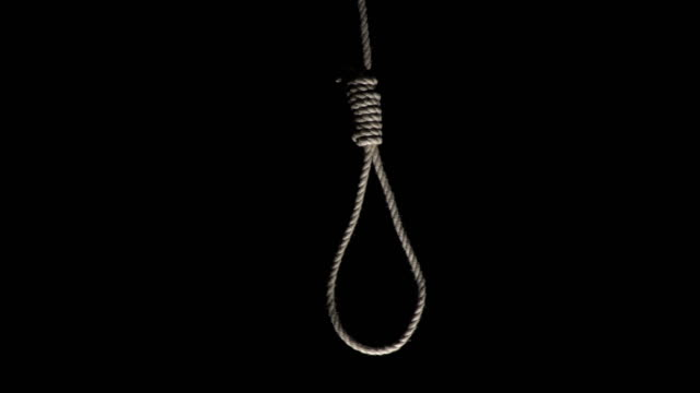 4K DOLLY: Rope Noose hanging on Black background Stock 4K video clip footage of a rope Noose hanging on a black background.  The rope is swinging a little. hanging stock videos & royalty-free footage
