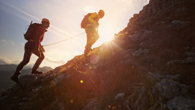 Rope team of two mountaineers climbing the mountain in setting sun