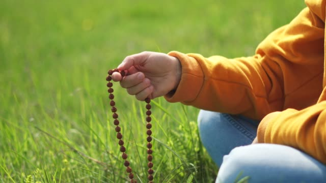 Rosary Beads. Harmony. Close-Up of A Hand Holding a Rosary While Saying a Prayer while being in the Nature. Religion