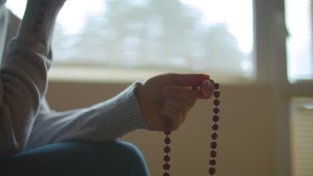 rosenkranz perlen. harmonie. nahaufnahme einer person, die einen rosenkranz hält, während sie ein gebet sagt. religion - islam stock-videos und b-roll-filmmaterial