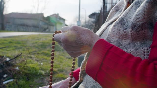 rosenkranz perlen. harmonie. nahaufnahme einer person, die einen rosenkranz hält, während sie ein gebet sagt. religion - religiöses symbol stock-videos und b-roll-filmmaterial