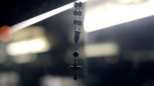 Rosary hanging, lights and traffic in the background video