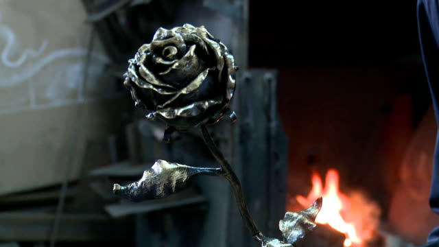 Rose from a metal furnace in the background Rose from a metal furnace in the background blacksmith stock videos & royalty-free footage