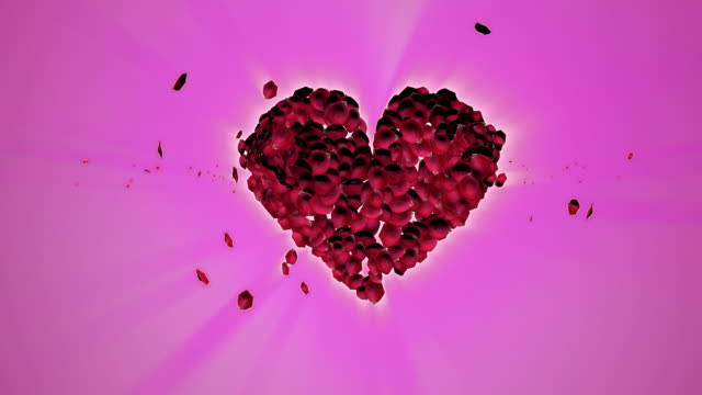 Rose petals falling down creating the shape of a heart.