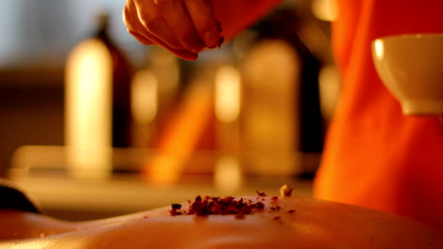 Rose petals spread on the skin – slow motion video
